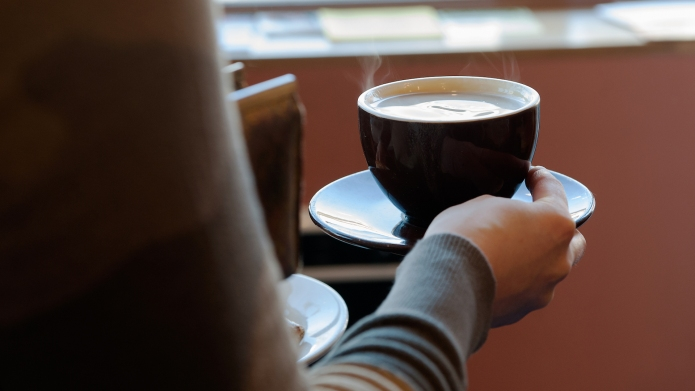 photo of woman holding hot coffee