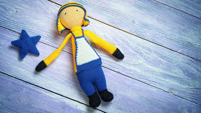 Handsome boy doll on blue wooden