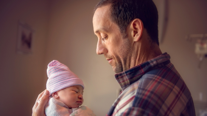 photo of father holding newborn baby