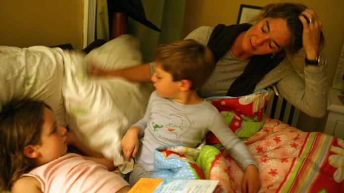 An exhausted mother rearranges the pillows