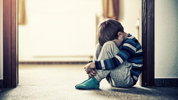 Sad little boy huddled in doorway