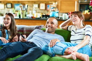 Happy family reclining on green sofa and watching TV
