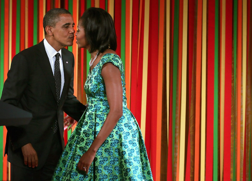 "WASHINGTON, DC - AUGUST 20: U.S. President Barack Obama kisses the first lady Michelle Obama as he visits her and the Kids' ""State Dinner"" luncheon event at the East Room of the White House August 20, 2012 in Washington, DC. Fifty-four kids representing all U.S. states, three territories and the District of Columbia, ages 8-12 and winners of the Healthy Lunchtime Challenge to create a healthy, affordable and tasty lunchtime recipe with nutritional guidelines set by the Agriculture Department, were invited to participate in the event. (Photo by Alex Wong/Getty Images)"