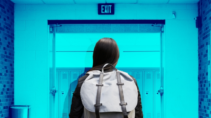 Teen with backpack in school hallway