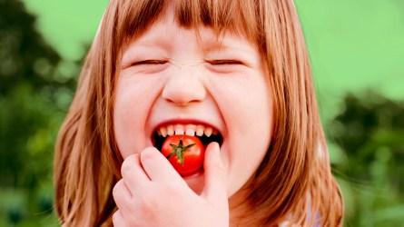 Girl eating tomato