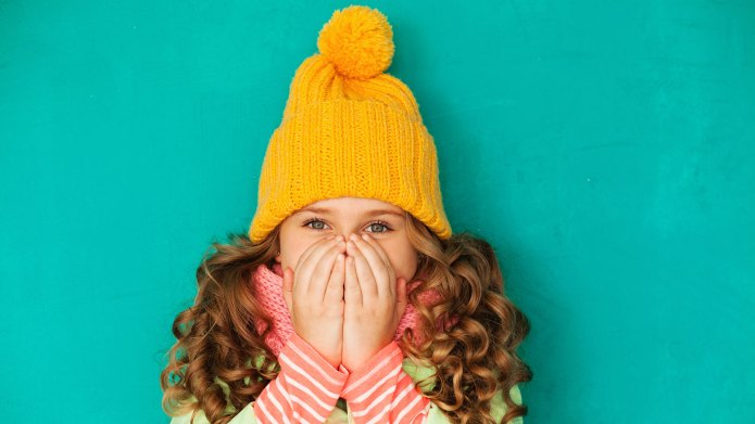 Girl covering her nose and mouth.