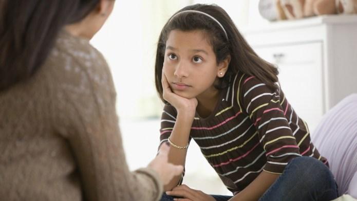 Mother talking to daughter in bedroom