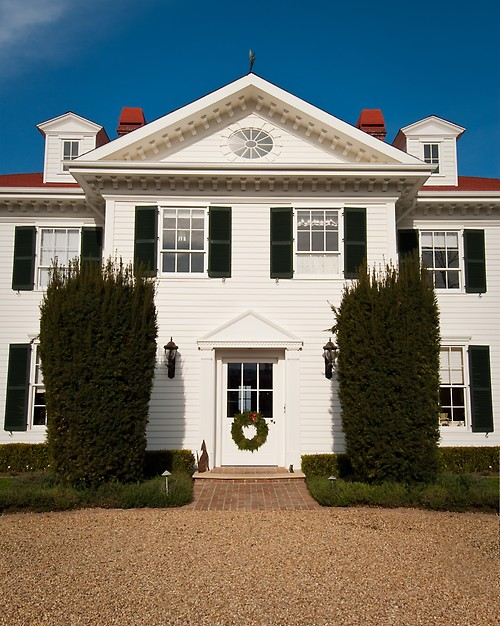 White colonial with a red roof and navy blue shutters