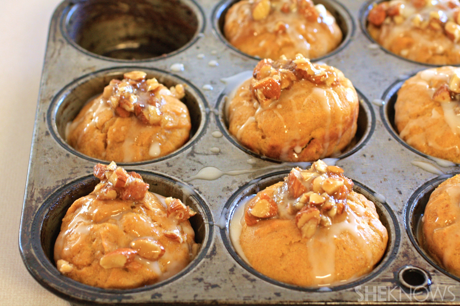 Pumpkin-chai muffins with vanilla glaze and maple-coated almonds