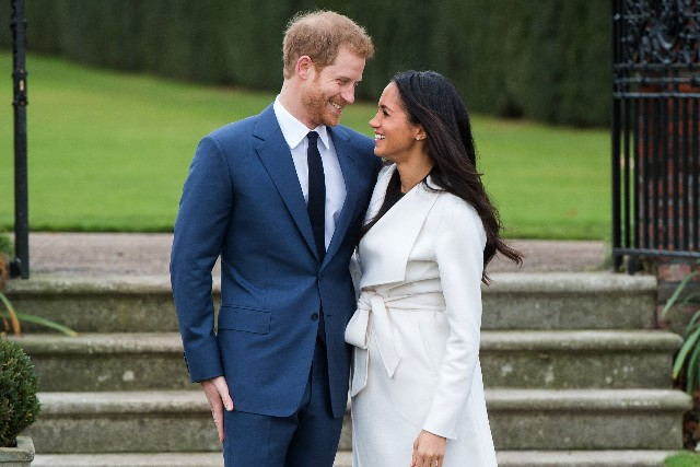 Prince Harry and Meghan Markle, wearing a white belted coat by Canadian brand Line The Label, attend a photocall in the Sunken Gardens at Kensington Palace following the announcement of their engagement