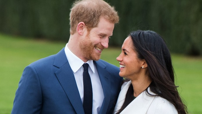 Prince Harry and Meghan Markle, wearing a white belted coat by Canadian brand Line The Label, attend a photocall in the Sunken Gardens at Kensington Palace