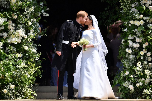 Britain's Prince Harry, Duke of Sussex kisses his wife Meghan, Duchess of Sussex as they leave from the West Door of St George's Chapel, Windsor Castle