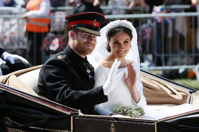Prince Harry, Duke of Sussex and Meghan, Duchess of Sussex wave from the Ascot Landau Carriage during their carriage procession on Castle Hill outside Windsor Castle