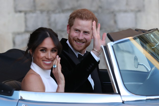 Meghan, Duchess of Sussex and Prince Harry, Duke of Sussex wave as they leave Windsor Castle after their wedding