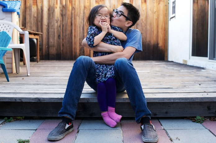 Father and daughter playfully hug and