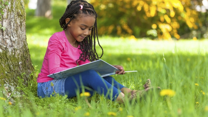 Cute young black little girl reading