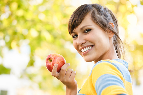 Happy Woman eating an apple