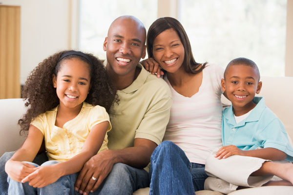 Healthy family sitting in living room smiling