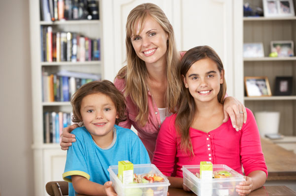 Mother and children with packed healthy lunches