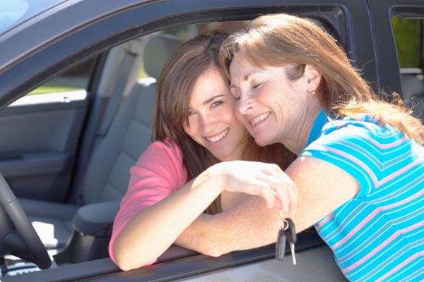 Mother embracing teenage girl holding keys