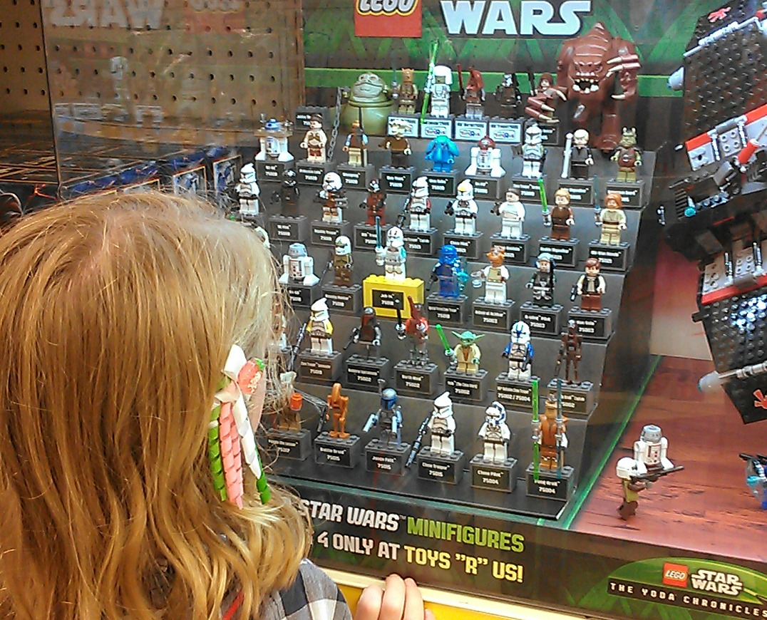 girl looks at LEGO minifigures