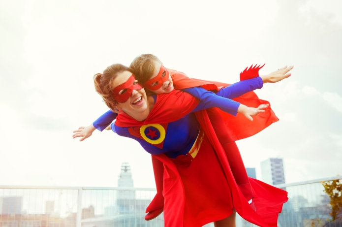 Superhero mother and daughter playing on
