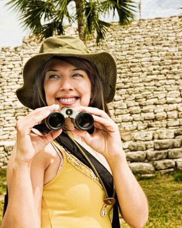 Woman with binoculars at Tulum ruins, Quintana Roo, Mexico