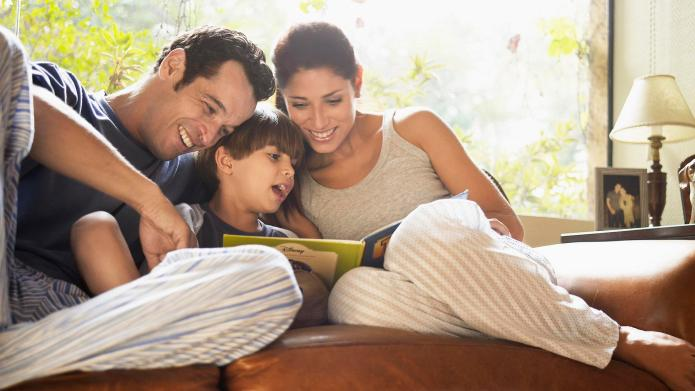 Parents and son reading book on
