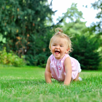 Baby crawing in grass