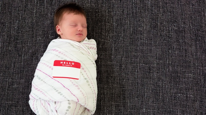 """Sleeping swaddled infant with a """"Hello"""