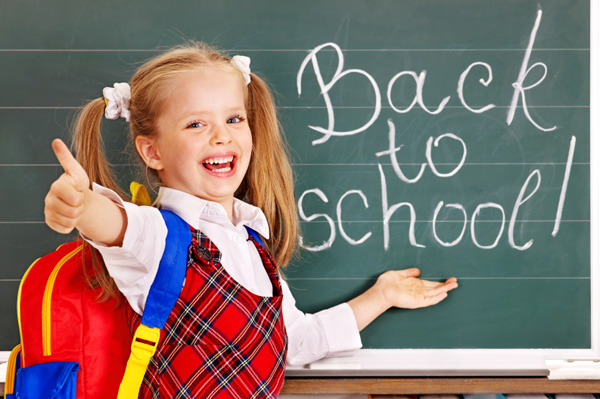 Back to school written on chalk board with girl giving thumbs up