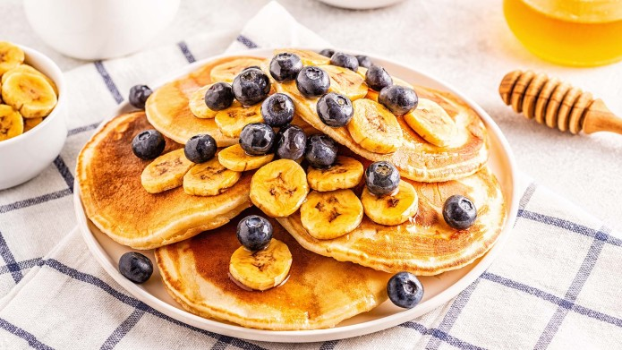 Pancakes with banana, blueberries on white