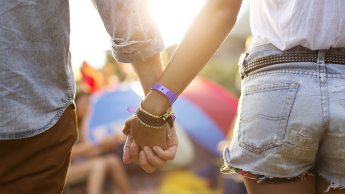 Couple holding hands near tents at