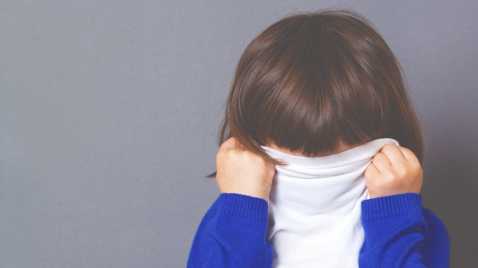 playful preschooler covering eyes with sweater