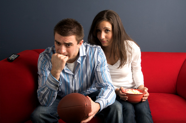 Bored woman watching football with husband