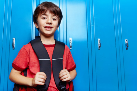 Boy in school with backpack