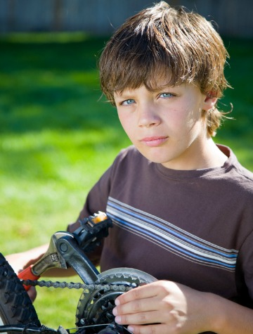 Boy with stuck bike chain