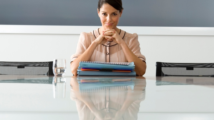 Businesswoman with files at boardroom table,