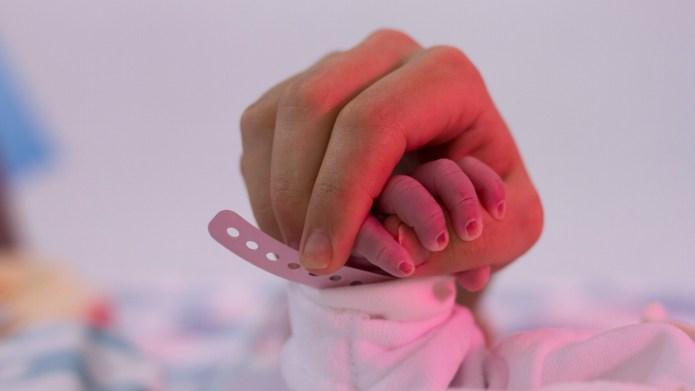 newborn grabs mother's finger