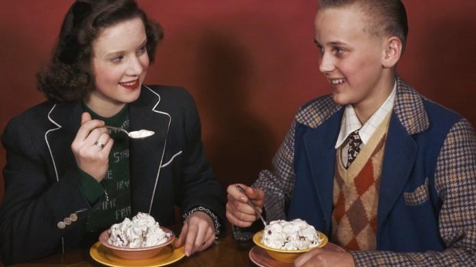 A teenage boy and girl flirt