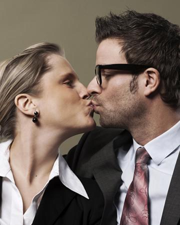 businesswoman kissing her husband