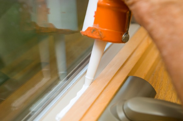 man caulking window sills