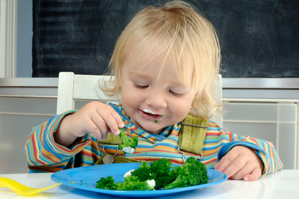 Child eating broccoli