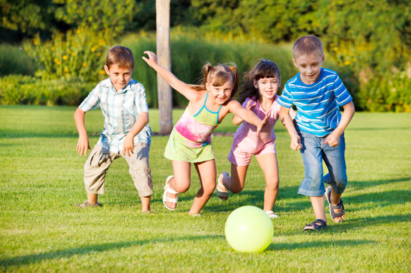 Children playing outside in backyard with ball