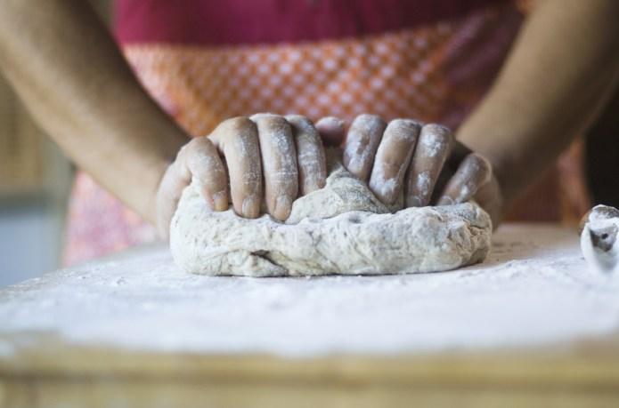 Mixed race woman kneading dough in
