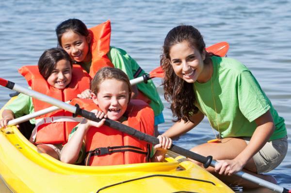 Camp counselor and kids kayaking