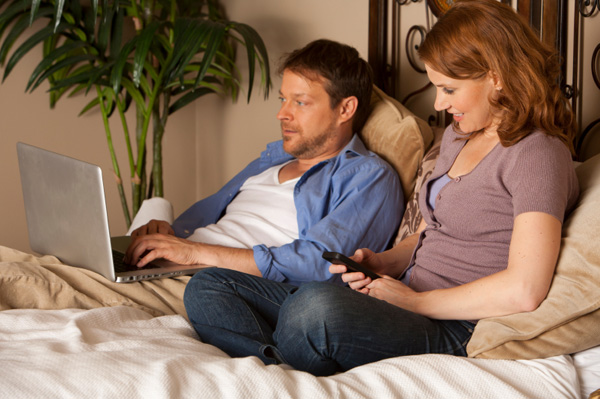 Couple on computer and smartphone in bed