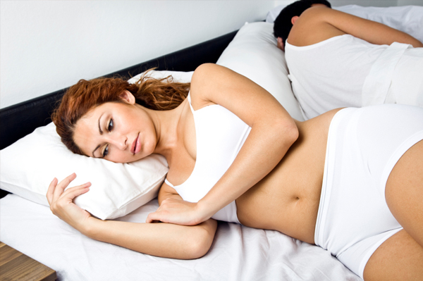 Tired woman in bed with spouse