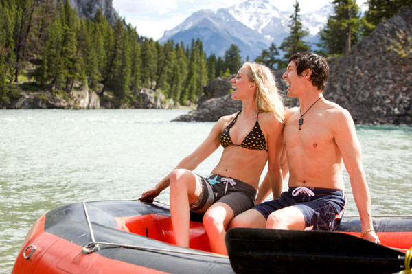 Couple resting on river bank while white water rafting together
