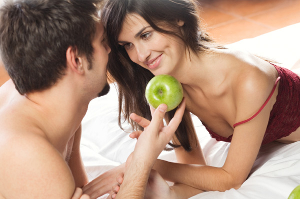 Couple with apple in bed